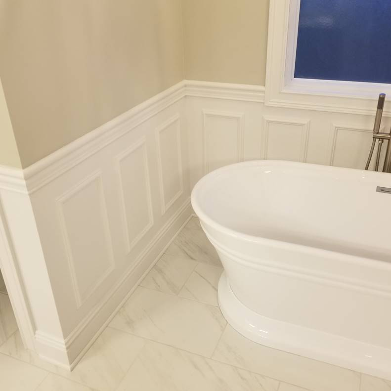A bathroom with a white tub sitting next to a window  Description automatically generated