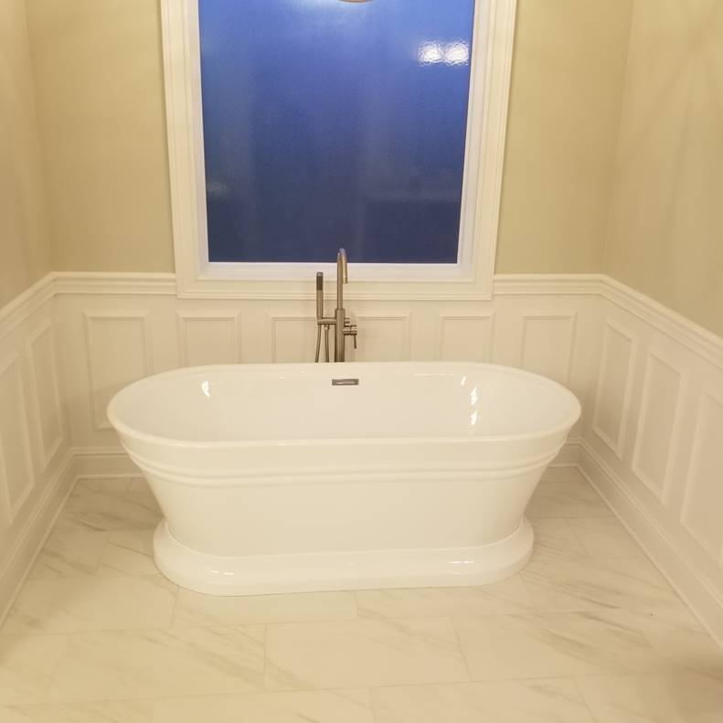 A bathroom with a white tub sitting next to a sink  Description automatically generated